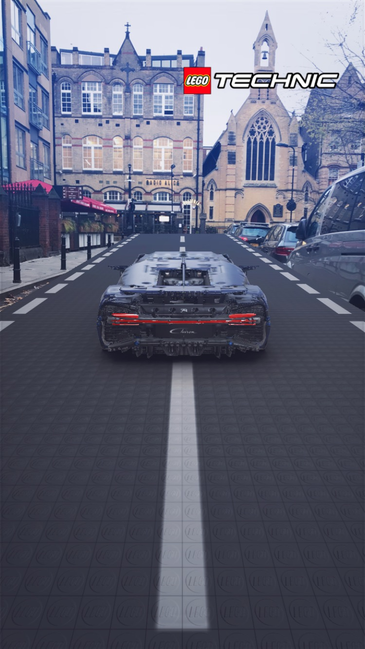 Read end of cartoon car in foreground on road superimposed on the screen flanked by real cars and pointing in the direction of a pizzeria and old, face-brick Catholic church in Hoxton Square, London